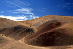 View on ridge of colorful red and black barren mountain contrasting with blue sky and white cirrus clouds royalty free stock images