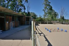 View of a riding school with horses boxes and rectangle. With horses obstacles Stock Photos