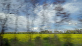 View from riding train window of coutryside landscape against cloudy sky stock footage