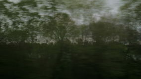 View from riding train window of coutryside landscape, trees, forests, houses against cloudy sky stock footage