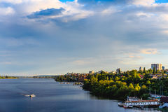 View of the right bank from the Voronezh reservoir. Water, lake, boat, dock, city with trees and houses. Panoramic view of the right bank from the Voronezh Royalty Free Stock Images