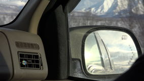 View of the right side mirror of the car in the mountains and snow-capped peaks of the northern slopes.  stock footage