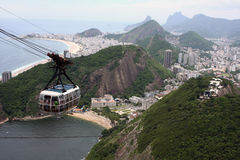View of Rio de Janeiro. Cable car descending from Sugarloaf Mountain; view of Copacabana Beach in the back Stock Photography