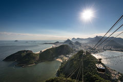 View of Rio de Janeiro From the Sugarloaf Mountain. View of Rio de Janeiro city from the Sugarloaf Mountain with sun in the sky and a cable car approaching Royalty Free Stock Image