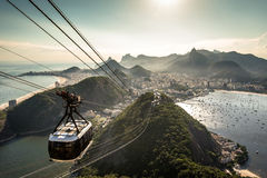 View of Rio de Janeiro From the Sugarloaf Mountain. View of Rio de Janeiro city from the Sugarloaf Mountain by sunset with a cable car approaching Royalty Free Stock Image