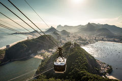 View of Rio de Janeiro From the Sugarloaf Mountain. View of Rio de Janeiro city from the Sugarloaf Mountain by sunset with a cable car approaching Royalty Free Stock Photo