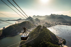 View of Rio de Janeiro From the Sugarloaf Mountain. View of Rio de Janeiro city from the Sugarloaf Mountain by sunset with a cable car approaching Stock Photos