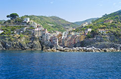 View of Riomaggiore - Italy. The small fishing village of Riomaggiore with its blue seas as seen from a boat Royalty Free Stock Photo
