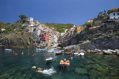 View of Riomaggiore village and young couple swimming Royalty Free Stock Photo