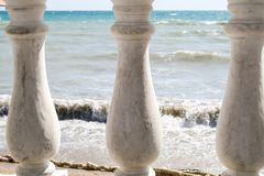 View of the rippling sea through three old pillars of the fence.  royalty free stock photography