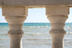 View of the rippling sea through old pillars of the fence. View of the rippling sea through two old pillars of the fence stock photos