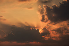 View of rising sunbeams from behind golden cumulus clouds Royalty Free Stock Images