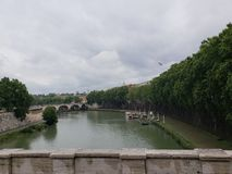 View of a river in the city of Rome, Italy on a cloudy day. European, travel, tourism, vacation, outdoor, water, trees, clouds, bridge, landscape, landmark royalty free stock images