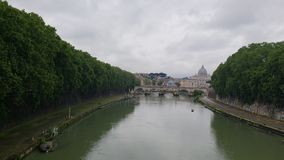 View of a river in the city of Rome, Italy on a cloudy day. European, travel, tourism, vacation, outdoor, water, trees, clouds, bridge, landscape, landmark stock image