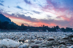 View of River Ganga and lots of stones after sunset with amazing dramatic sky. Royalty Free Stock Images