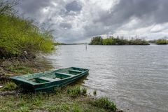 View of the river with grass and boat, in Porto do sabugueiro, muge, santarem portugal stock photo