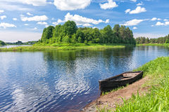 View on river with island and wooden boat laid up on riverbank Stock Photo