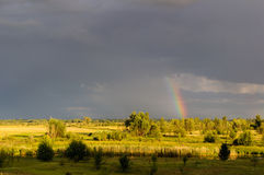 View of the river and the rainbow after a thunderstorm at sunset Royalty Free Stock Images