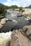A view of the river rapids and the rapid water flow of the Yuzhny Bug River in the summer. A view of the river rapids and the rapid water flow of the Southern Stock Photos