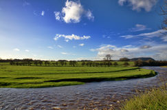 View of the River Ribble and fields, Clitheroe. A peaceful view of the River Ribble, near Clitheroe, Lancashire, running through verdant green meadows, and set Royalty Free Stock Images