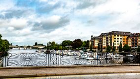 View of the river Shannon through the fence of the blacksmith. Boats anchored at the dock with the railway bridge in the background, town of Athlone in the royalty free stock photography