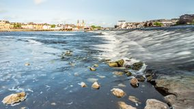 View of the river Shannon with its crystal clear waters and stones on the shore. With the town of Athlone in the background, wonderful cloudy day in the county stock images