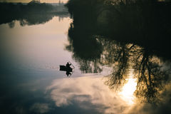 View river an silhouette fisherman in boat sailing Royalty Free Stock Photography