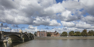 A view of the river Thames. This picture shows a view of the river Thames. There's a Chelsea Bridge visible on the left and some redbrick buildings on the royalty free stock photography