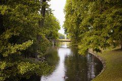 View of river and trees at Hofgarten park. Lush green space with meadows & formal flowerbeds, plus a pond, bandstand stock photo