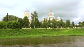 View of the river Tvertsu and the cathedral Transfiguration of the Savior on a cloudy july day. Torzhok, Russia. View of the river Tvertsu and the cathedral stock video footage