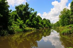River and Trees with Reflection of White Clouds in Blue Sky. View of river and vegetation at Horton Slough Park in Oklahoma. White clouds in bright blue sky and Royalty Free Stock Photo