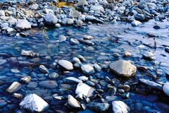 A view of a river water between stones. With beautiful colours Royalty Free Stock Photos