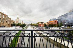 Urban landscape on rainy day. View of the river Yauza through the bridge Visokoyauzskiy, Moscow, Russia. View of the river Yauza and roadways of its both royalty free stock image