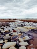Stones on Riverbed. View of riverbed flowing out into sea Stock Images