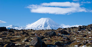 A view on a road and active volcano Ngaruahoe. Basaltic lava fields and Mount Ngaruahoe with white clouds. Tongariro National Park, North Island, New Zealand Royalty Free Stock Photography