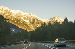 View of road with car at sunset in winter Switzerland Royalty Free Stock Images