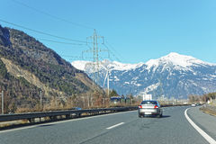 View of road with a car in Switzerland in winter. Switzerland is a country in Europe. Switzerland has a high mountain range; from the Alps to Jura mountains Royalty Free Stock Photography
