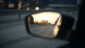 View of the road in the rearview mirror of a car at sunset stock video footage