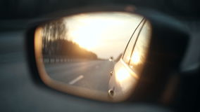 View of the road in the rearview mirror of a car at sunset stock video