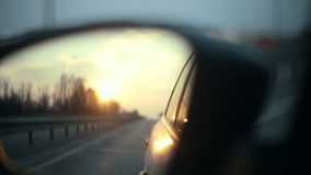 View of the road in the rearview mirror of a car at sunset stock footage