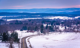 View of road through snow-covered fields and distant mountains, Stock Photos