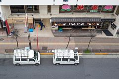 View of the road in takadanobaba, with two van parked on side of street stock image