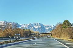 View from road to snow covered Swiss mountains Royalty Free Stock Image