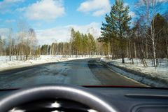 View of the road through the windshield. Snow on the sidelines. Wet asphalt road. Blue sky with clouds. Point of view of the