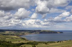 Robin Hoods Bay. View of Robin Hoods Bay across the fields from Ravenscar with cloudscape royalty free stock images