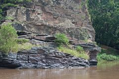VIEW OF ROCK FACE NEXT TO FLOWING RIVER. View of sheer rugged rough rocky cliffs next to a smoothly flowing river Royalty Free Stock Photography