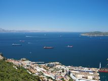 View from the Rock of Gibraltar of container and cargo ships. Passing through the Strait of Gibraltar with Morocco in the distance Royalty Free Stock Image