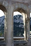 View of rocks through an arch. View of the huge rocks Montserrat through a big antique arch stock images