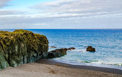 View of rocks at Black Beach and North Atlantic Ocean Royalty Free Stock Photography