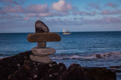 View of rocks on shore and sailing ship royalty free stock image